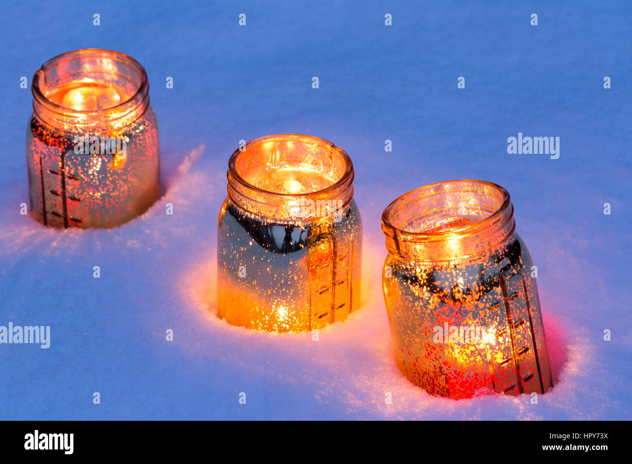 Decorative jar lanterns with candles glowing in snow Stock Photo