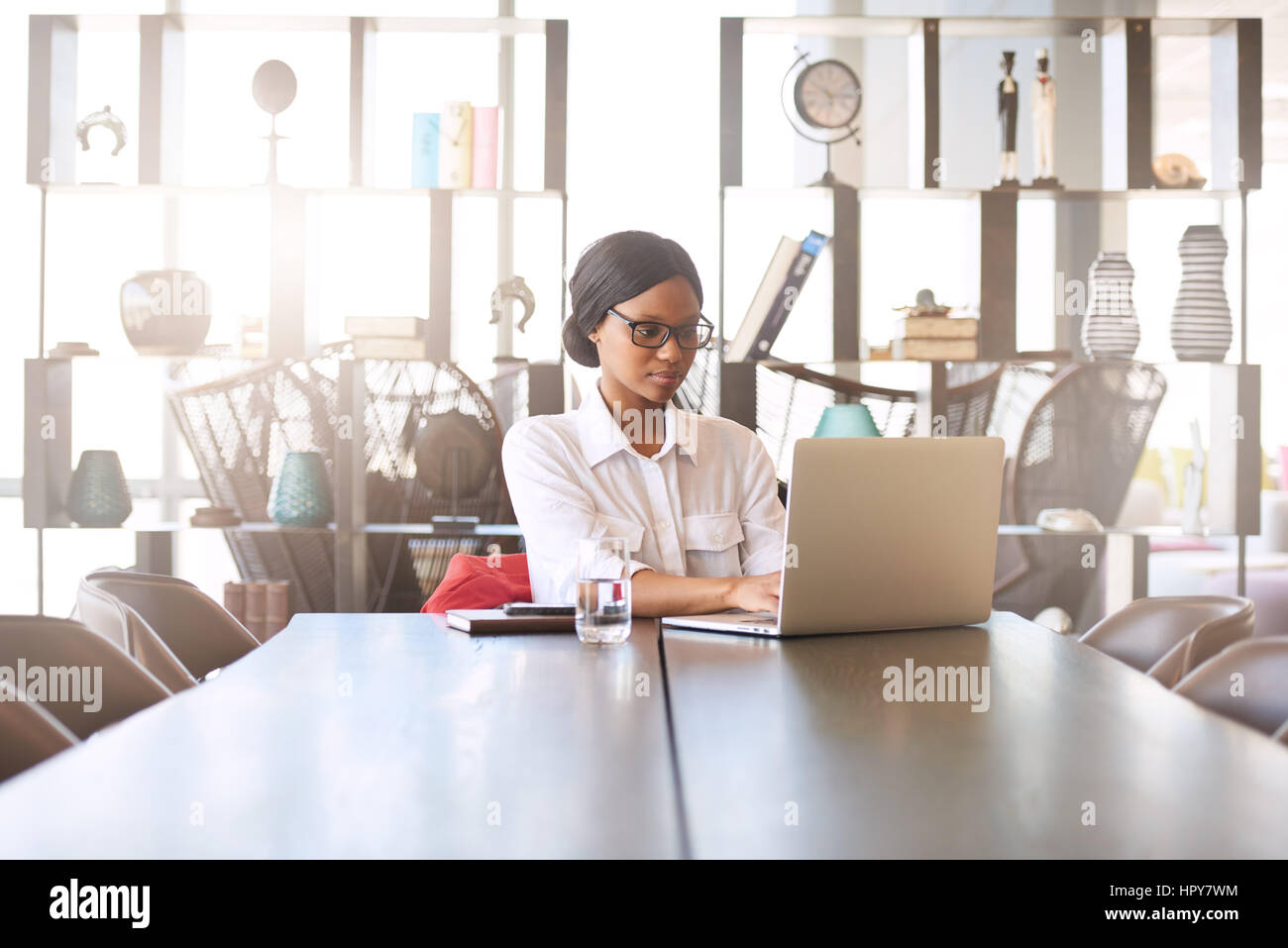 Attractive young professional well educated black woman busy typing on her notebook while seated at her dining room - Stock Image