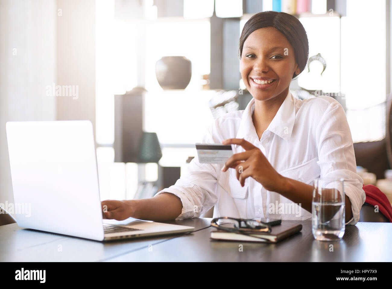 Good looking young black woman smiling at the camera while seated in front of her computer at her dining room table - Stock Image