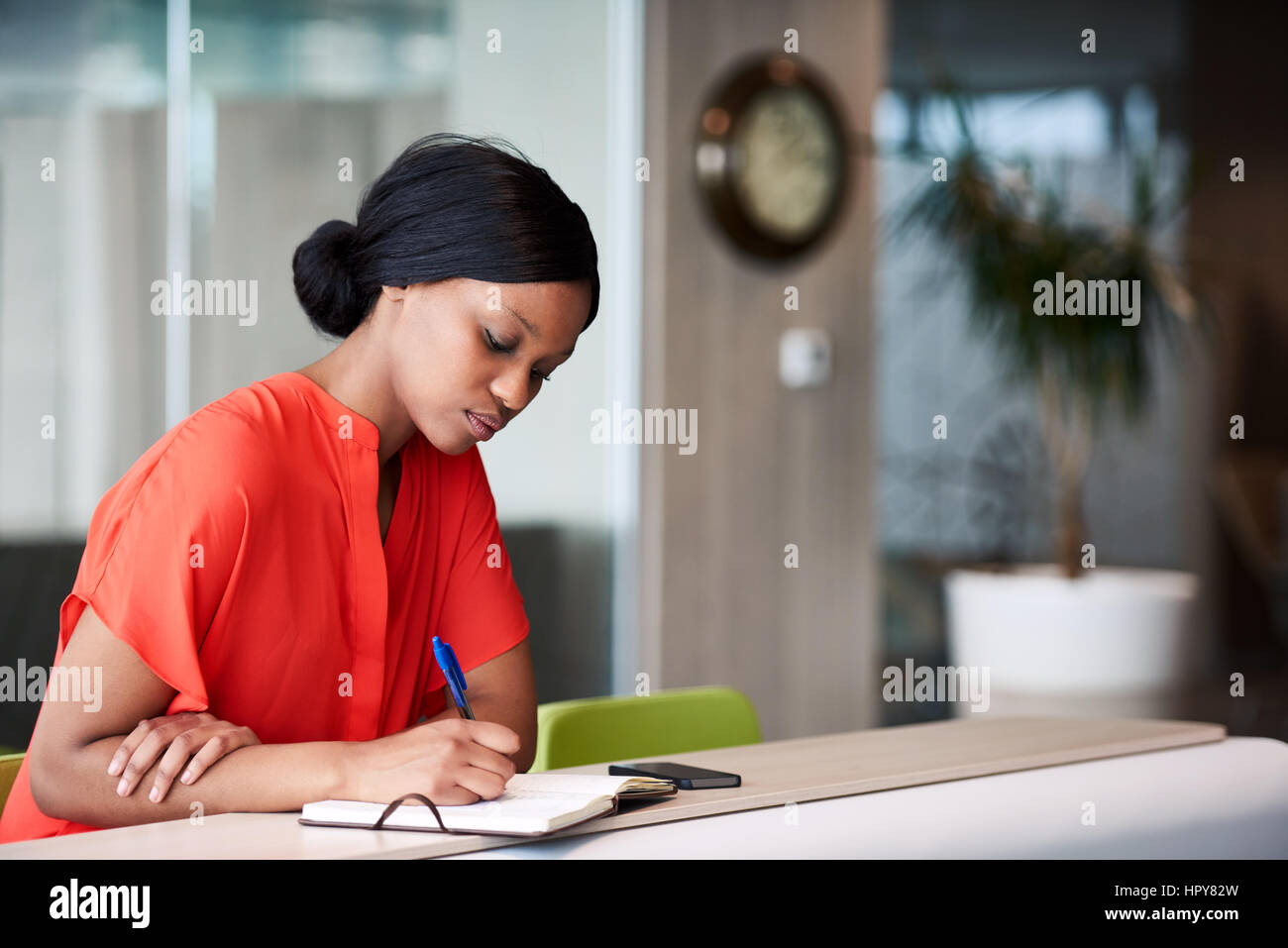Authentic image of African American woman busy using a pen to write down her shedule that she has planned out in Stock Photo
