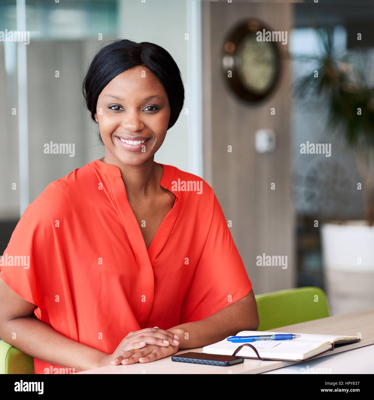 Square image of happy african woman smiling while looking into camera while wearimg a colourful orange blouse and - Stock Image