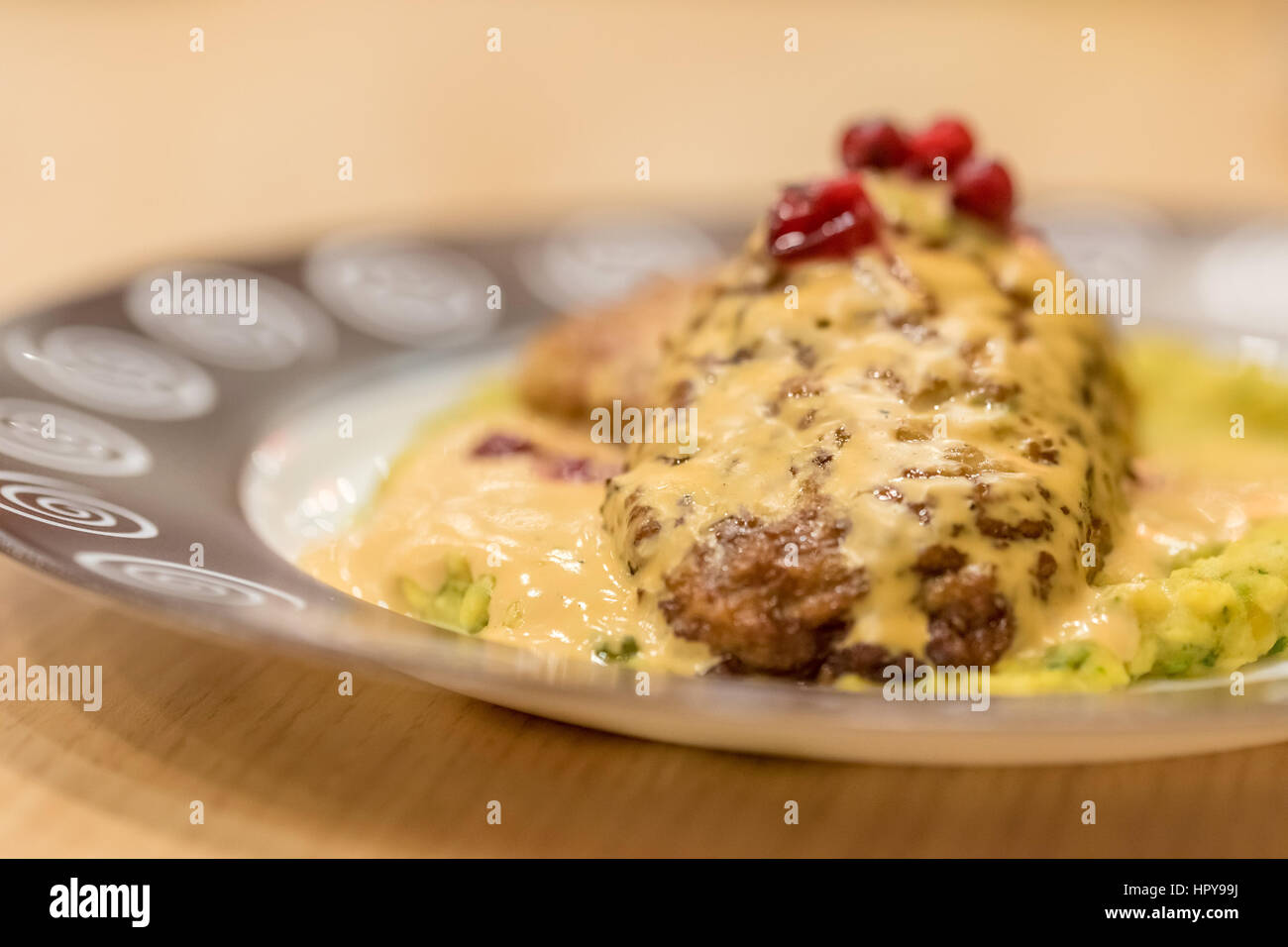 Meat patties or frikadeller in chese and mushroom sauce decorated with berries - Stock Image