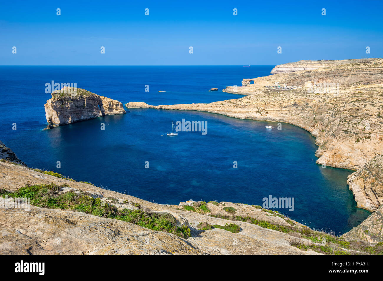 Gozo, Malta - Panoramic skyline view of Dwejra bay with Fungus Rock, Azure Window and sailboat on a nice hot summer Stock Photo