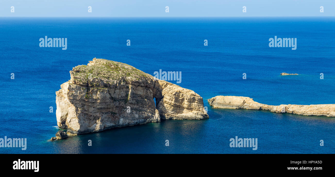 Gozo, Malta - The famous Fungus Rock on the island of Gozo on a beautiful hot summer day with crystal clear blue - Stock Image