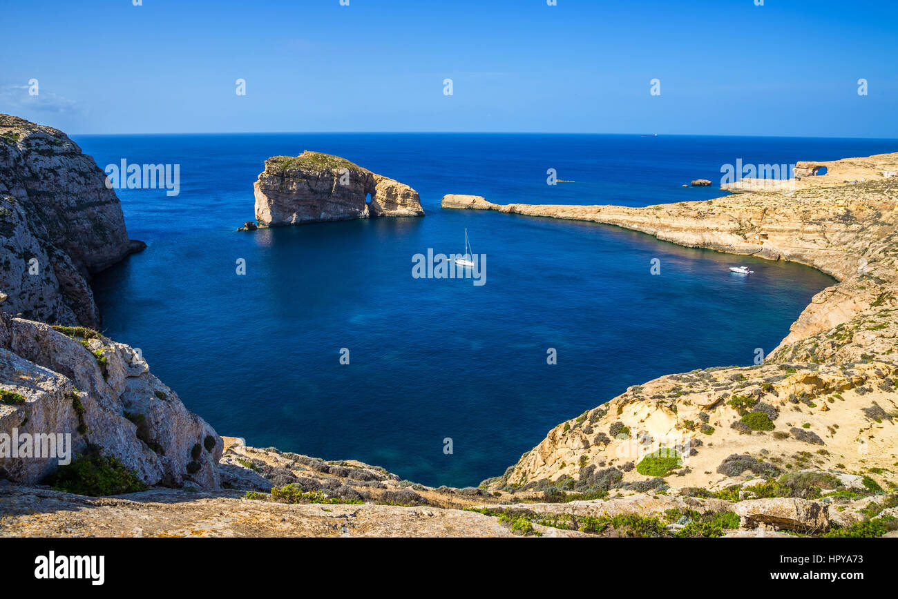 Gozo, Malta - Panoramic skyline view of Dwejra bay with Fungus Rock, Azure Window and sailboat on a nice hot summer - Stock Image