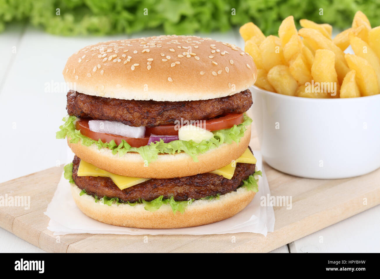 Double burger hamburger with fries tomatoes lettuce cheese unhealthy - Stock Image