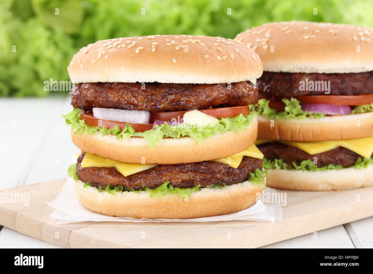Double burger hamburger tomatoes cheese unhealthy eating - Stock Image