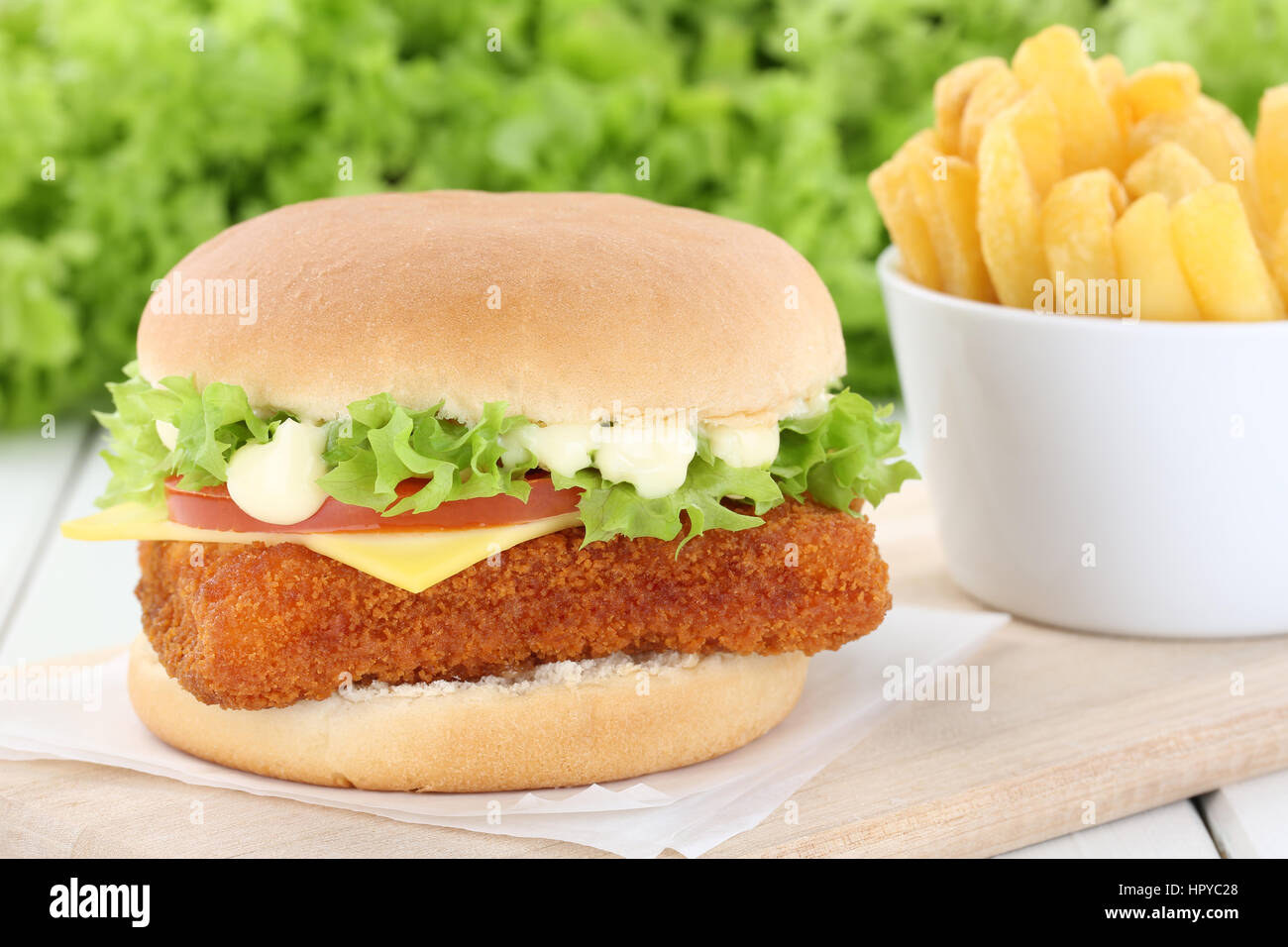 Fish burger fishburger hamburger with fries tomatoes lettuce cheese unhealthy - Stock Image