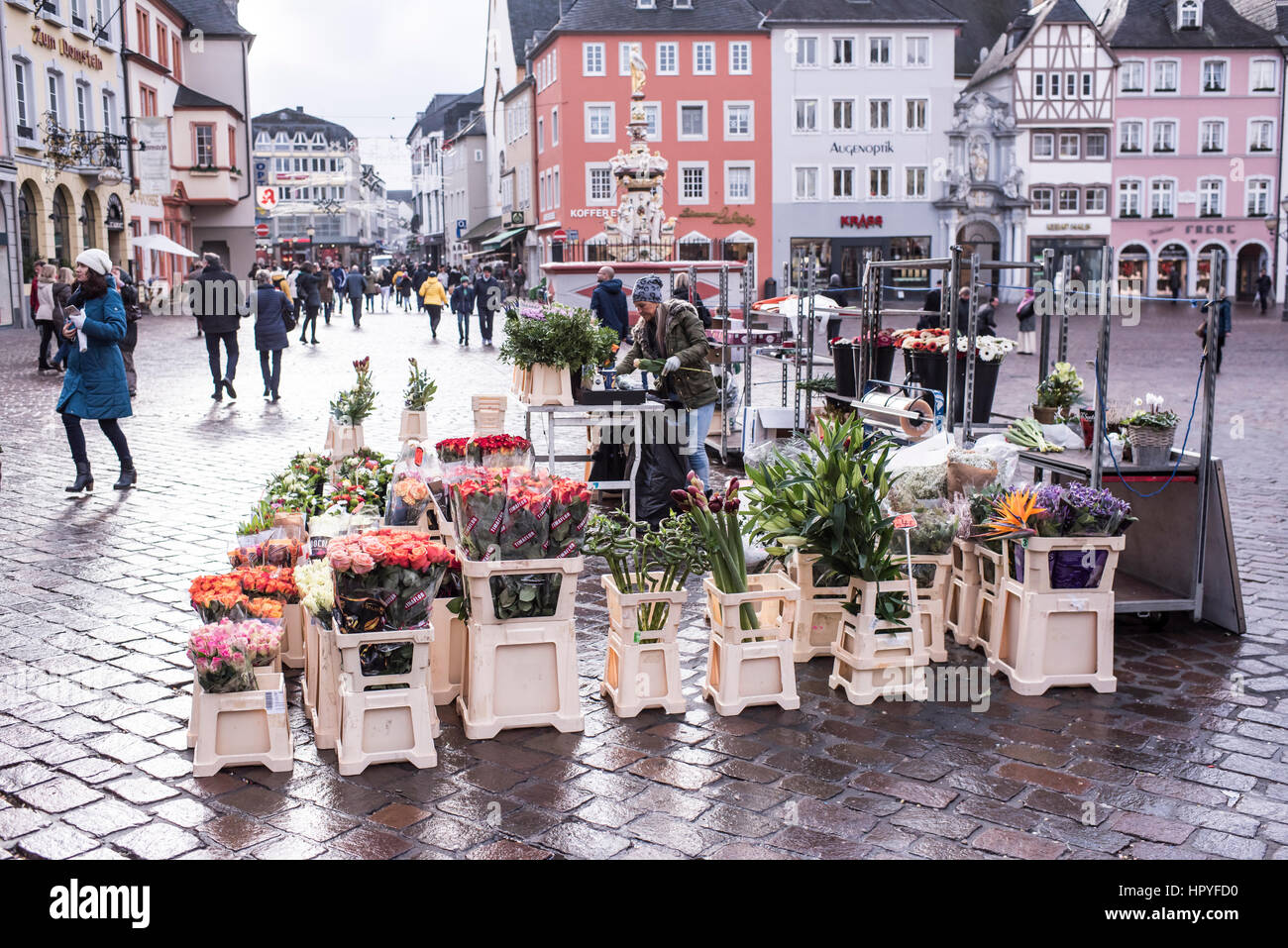 Trier,Germany- January 03, 2017: Dealers sell flowers on the market square. Tourists strolling through the square - Stock Image