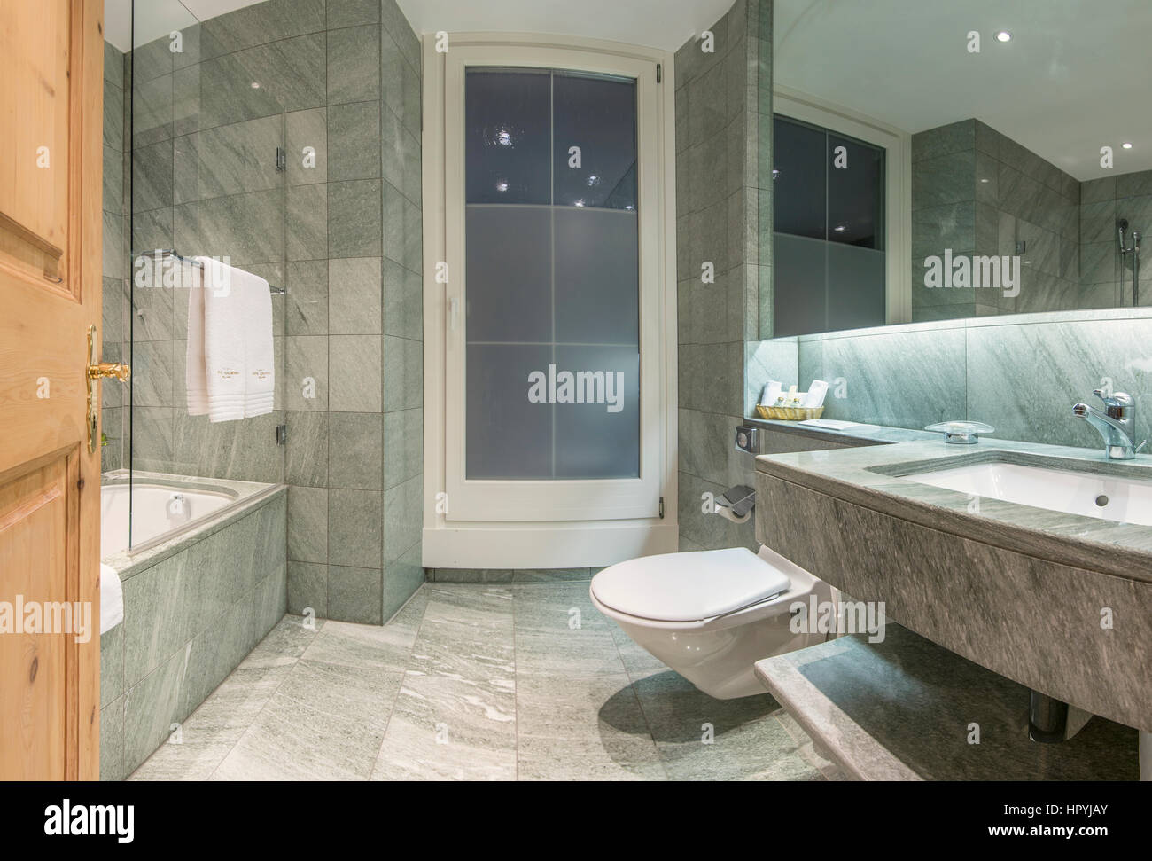 Modern minimalistic hotel bathroom with marble tiles covered walls interiors Stock Photo