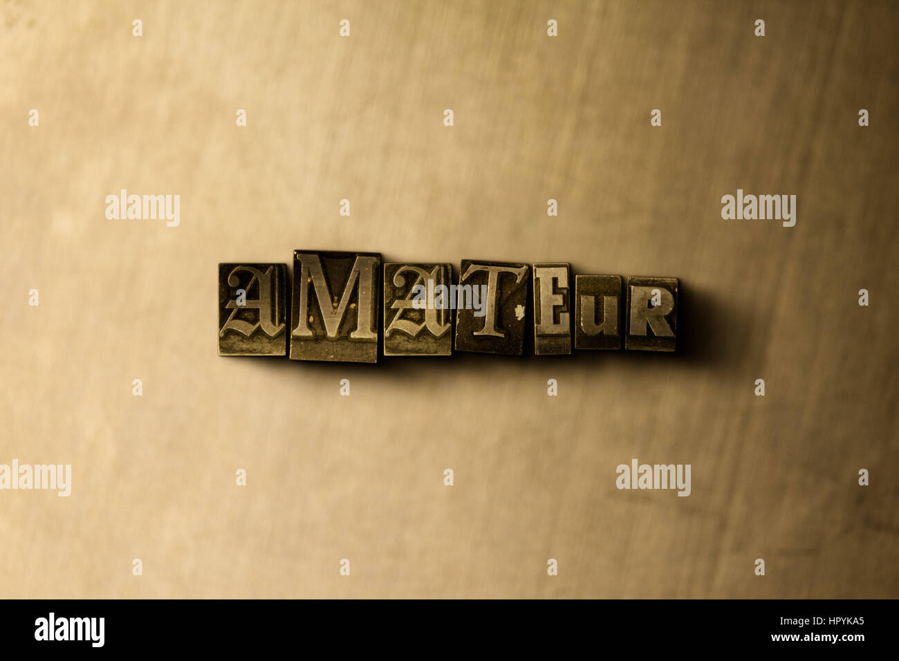 AMATEUR - close-up of grungy vintage typeset word on metal backdrop.  Royalty free
