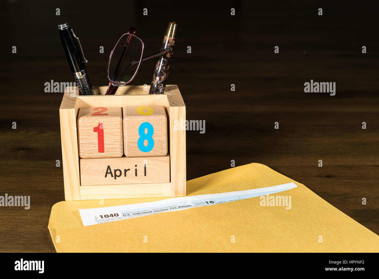 Wooden letters in calendar with Form 1040 income tax for 2016 showing tax day for filing is April 18 2017 Stock Photo