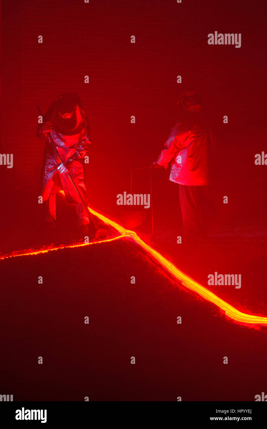 Pouring hot, glowing, molten iron across an earthen floor by two steelworkers, two reenactors recreating a metalurgical - Stock Image
