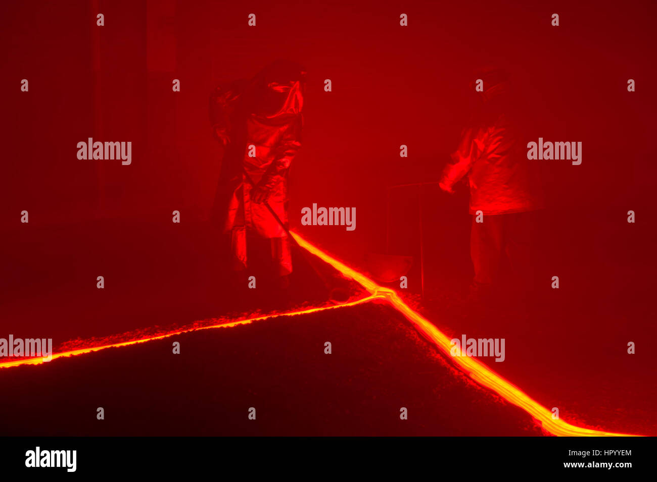 Pouring hot, glowing, molten iron across an earthen floor by two steelworkers, two reenactors recreating a metallurgical - Stock Image