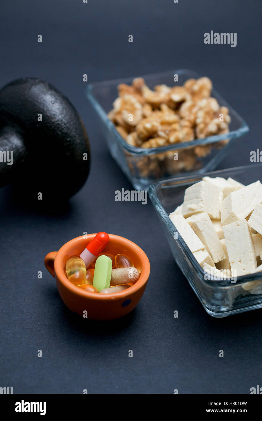 Dumbbell, walnut, tofu and dietary supplements on dark background: fitness and weight loss concept. - Stock Image