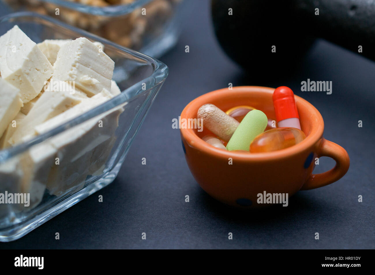 Closeup on dumbbell, walnut, tofu and dietary supplements on dark background: fitness and weight loss concept. - Stock Image