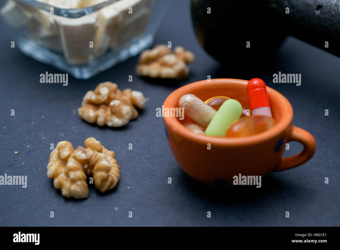 Dumbbell, walnut, tofu and dietary supplements on dark background: fitness and weight loss concept. Stock Photo