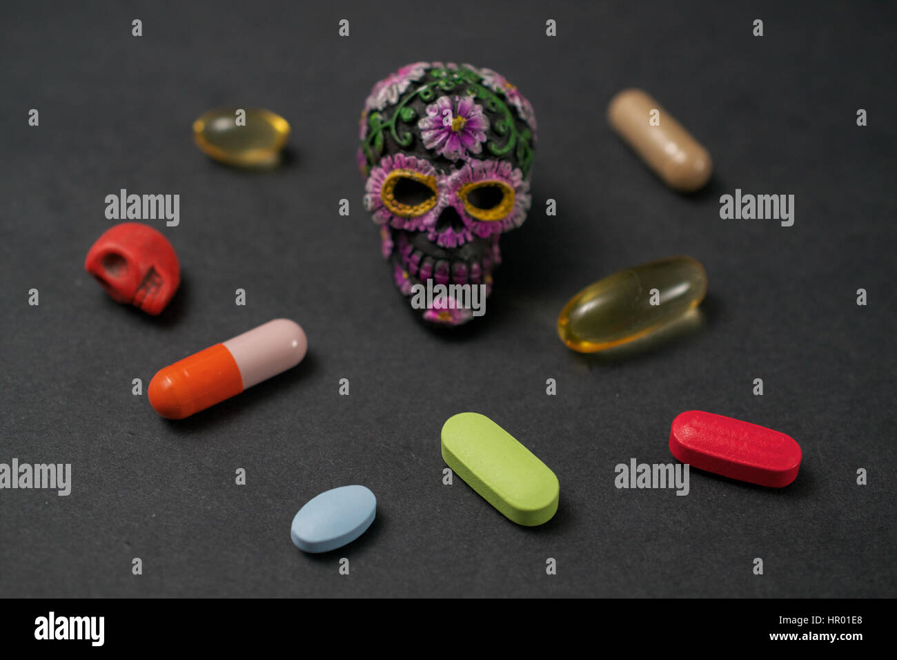 Prescription pills and dietary supplements surrounding a mexican day of the dead skull (calavera) suggesting the - Stock Image