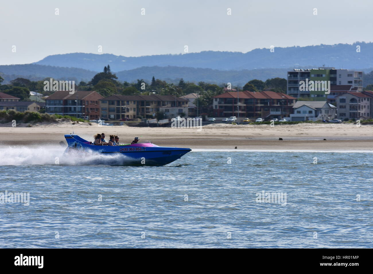 Jet speedboat cruising on water with townhouses and apartment buildings on shore in background. - Stock Image