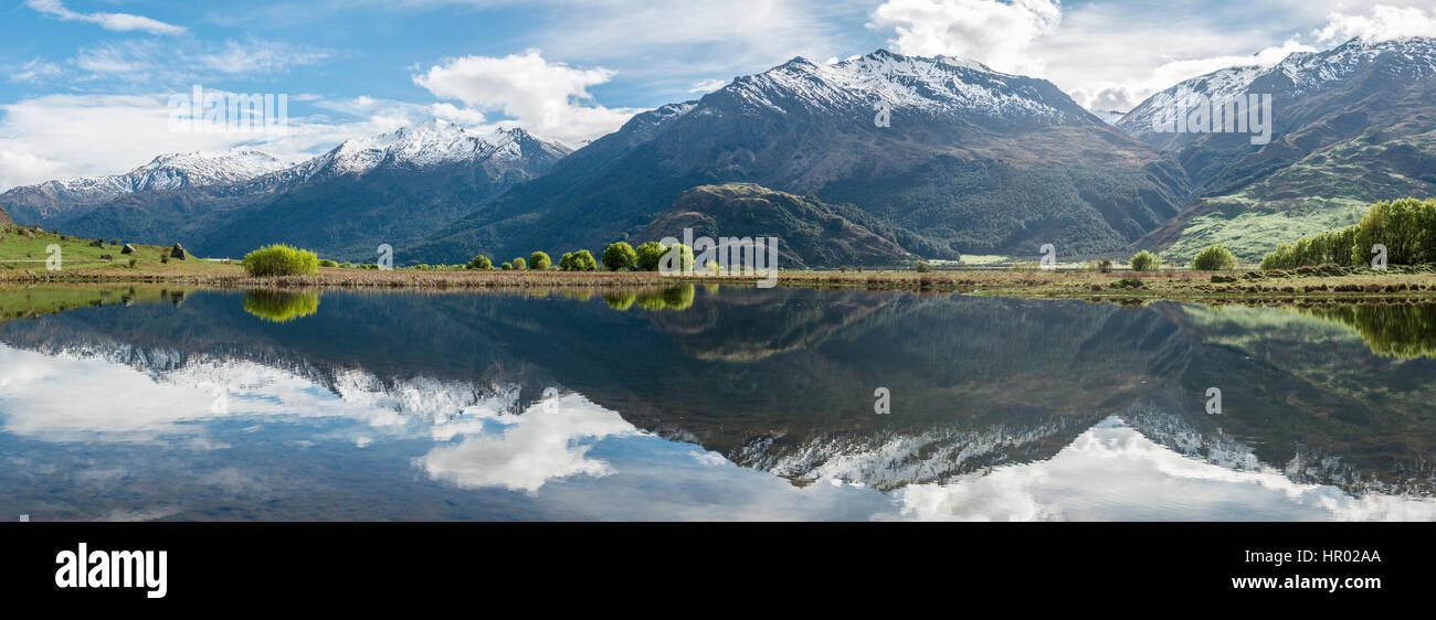Mountain range reflected in a lake, Matukituki Valley, Mount Aspiring National Park, Otago, Southland, New Zealand - Stock Image