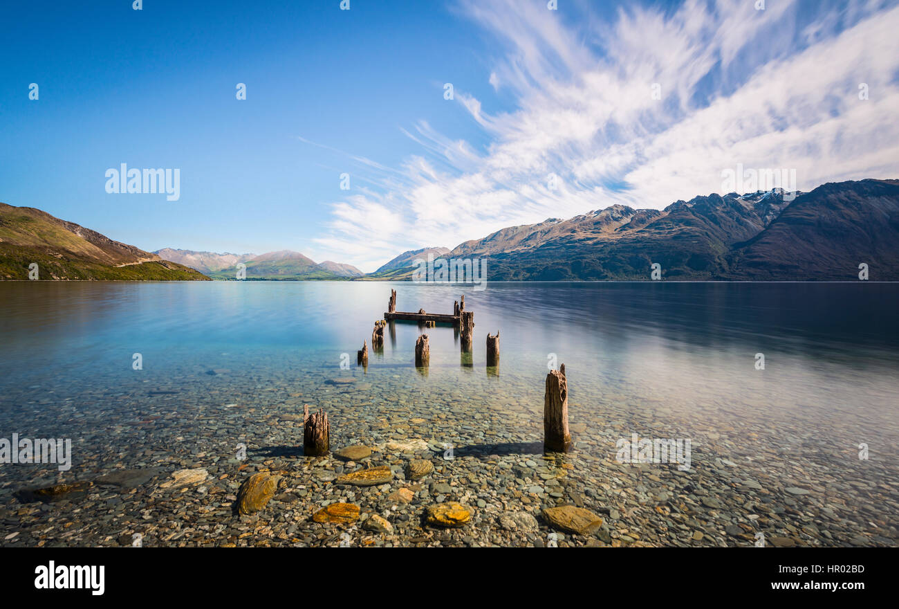 Decayed jetty, old wooden posts in Lake Wakatipu at Glenorchy, Otago Region, Southland, New Zealand - Stock Image