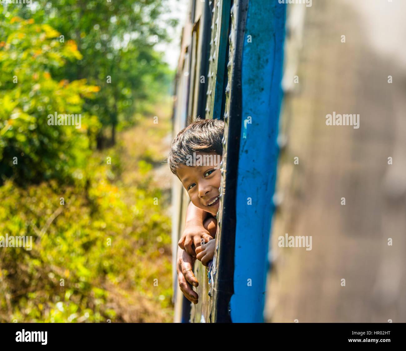 Small local boy looking out of moving train, Yangon Circular Railway, Yangon, Myanmar - Stock Image