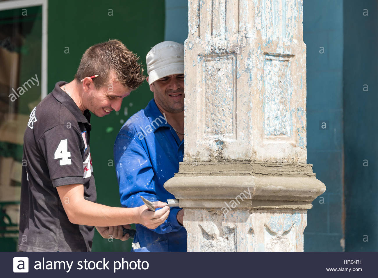 Cuban real people lifestyle: men working restoring old colonial column in the Calixto Garcia plaza surrounding buildings. - Stock Image