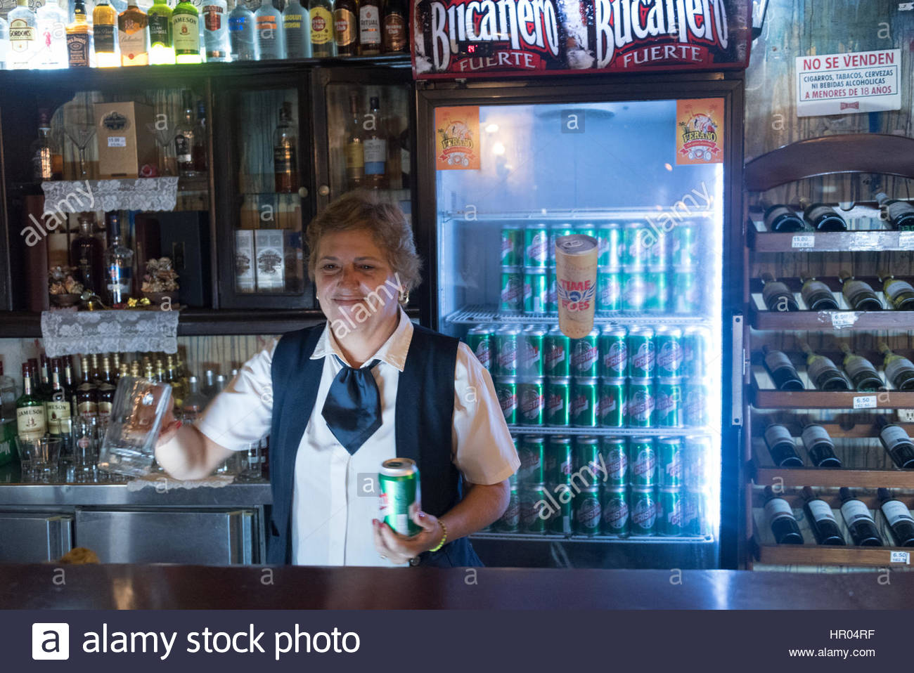 Cuban real people lifestyle: woman gastronomic waitress serving a Cristal beer in 'El Cambio' traditional - Stock Image