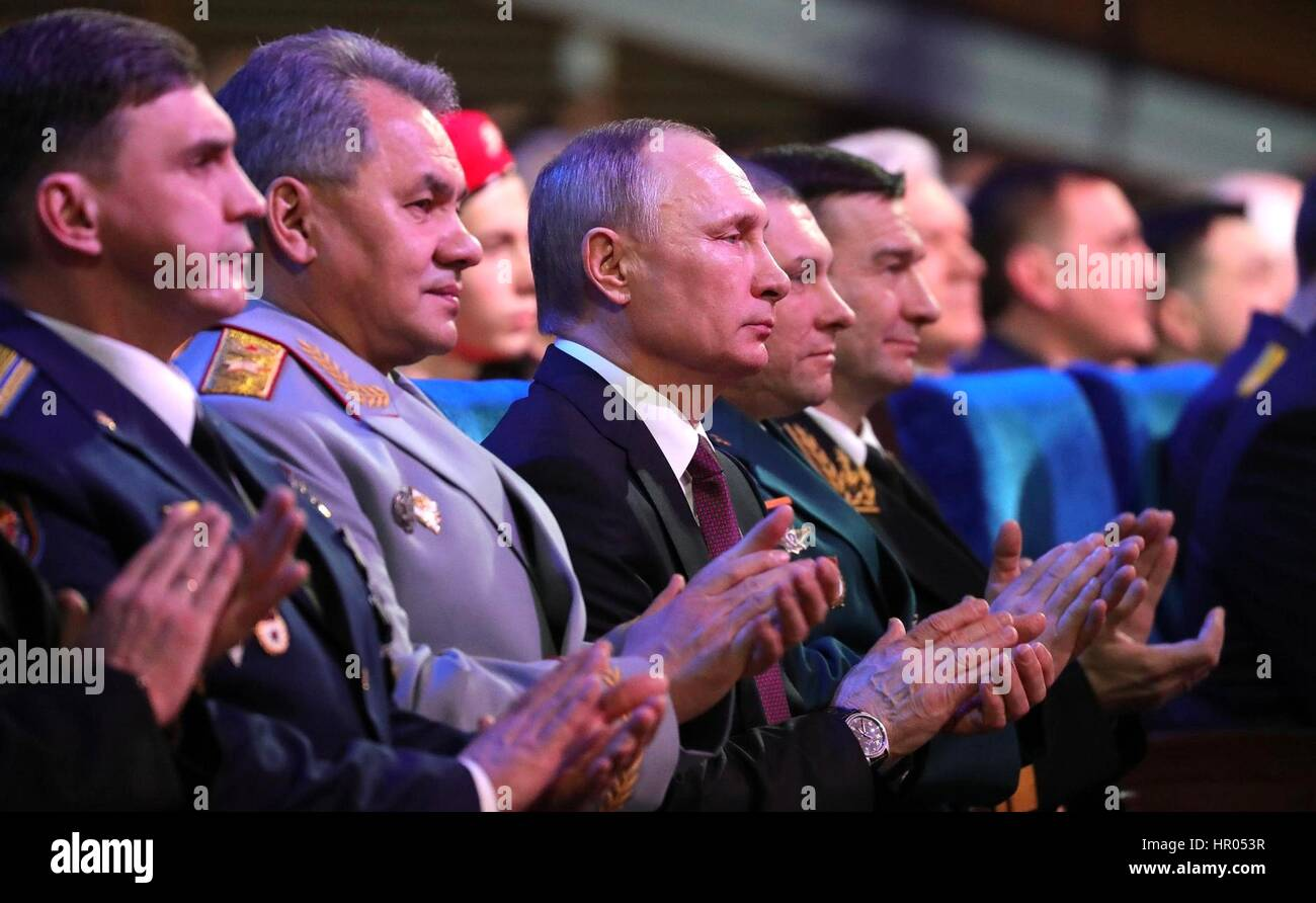 Russian President Vladimir Putin and Defense Minister Sergei Shoigu, left, applaud during a gala to mark Defender - Stock Image