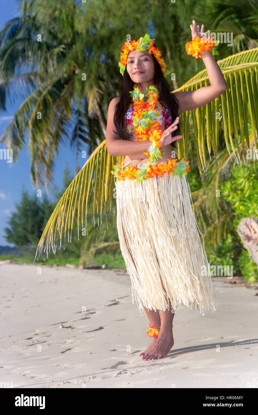 Hula Hawaii dancer dancing on the beach with palms trees. Ethnic woman in costume dancer Hawaii hula dancing in Stock Photo