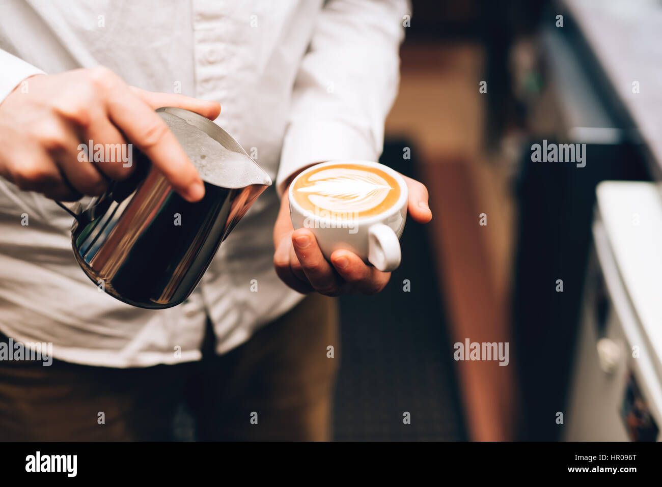 Barista pouring perfect cappuccino into cup, making a delicious morning drink - Stock Image