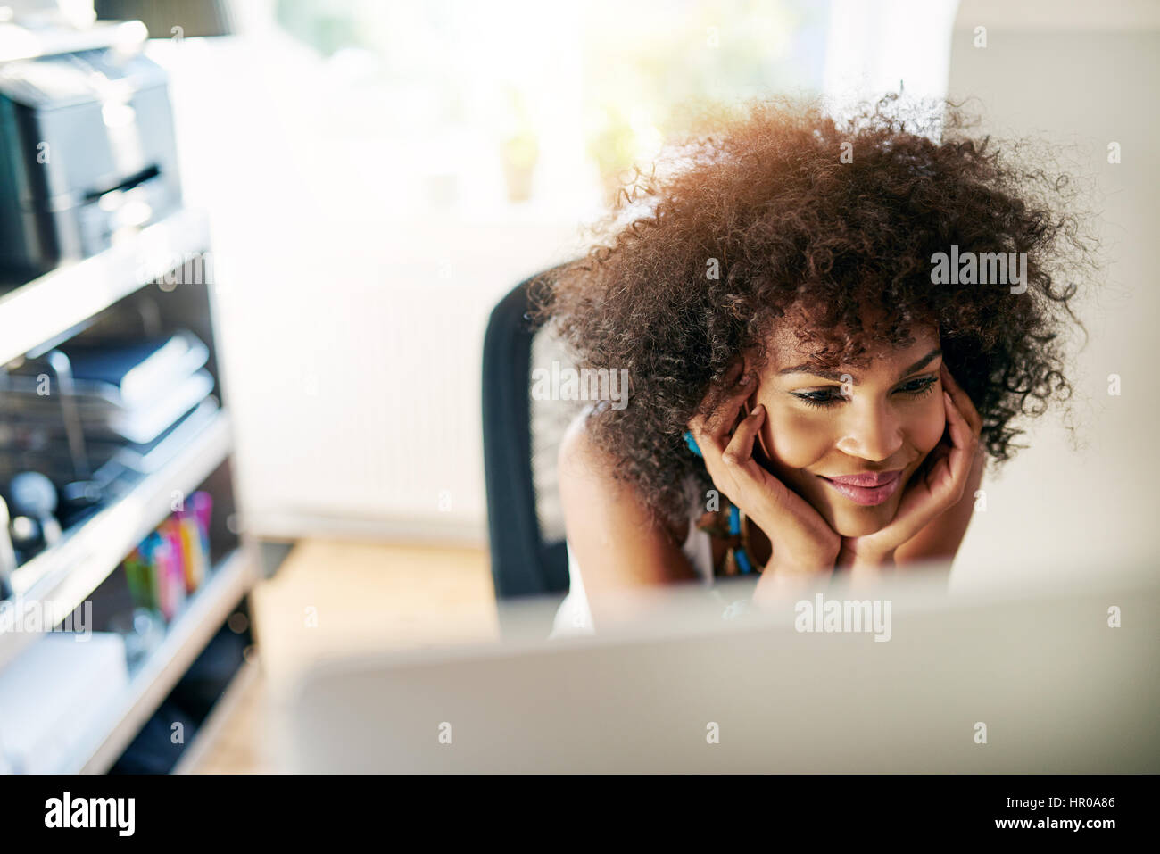 Young pretty afro-american woman looking at desk-top and smiling on blurred inside background. - Stock Image