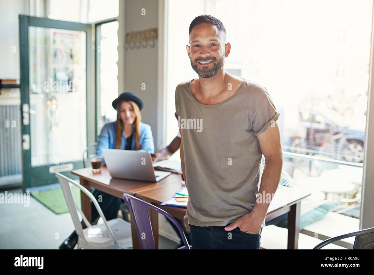 Young casual looking man with hand in pocket looking at camera on background of people at table. - Stock Image