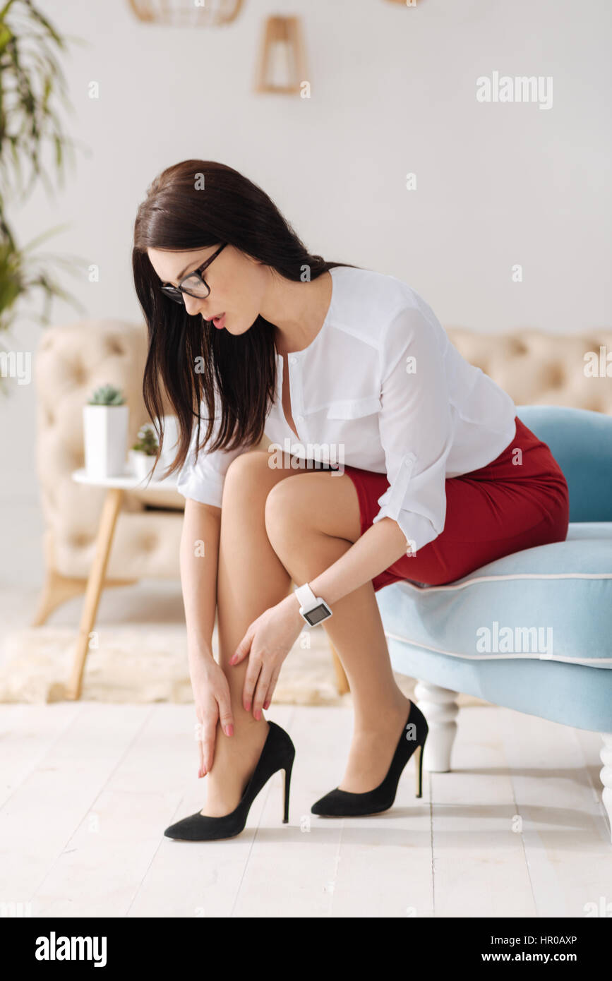 Wearing high heels. Elegant charming brunette woman sitting on the chair and looking at her shoes while putting - Stock Image