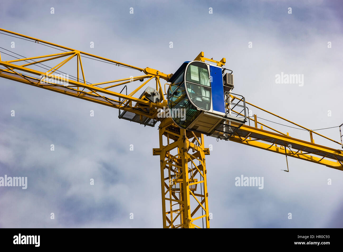 construction tower crane cabin closeup on blue sky with clouds