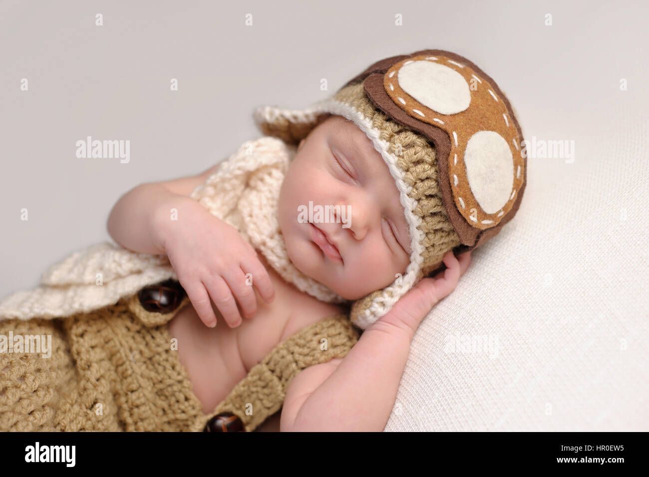 Sleeping two week old newborn baby boy wearing a crocheted aviator hat with  goggles. 4b41a2e53b07