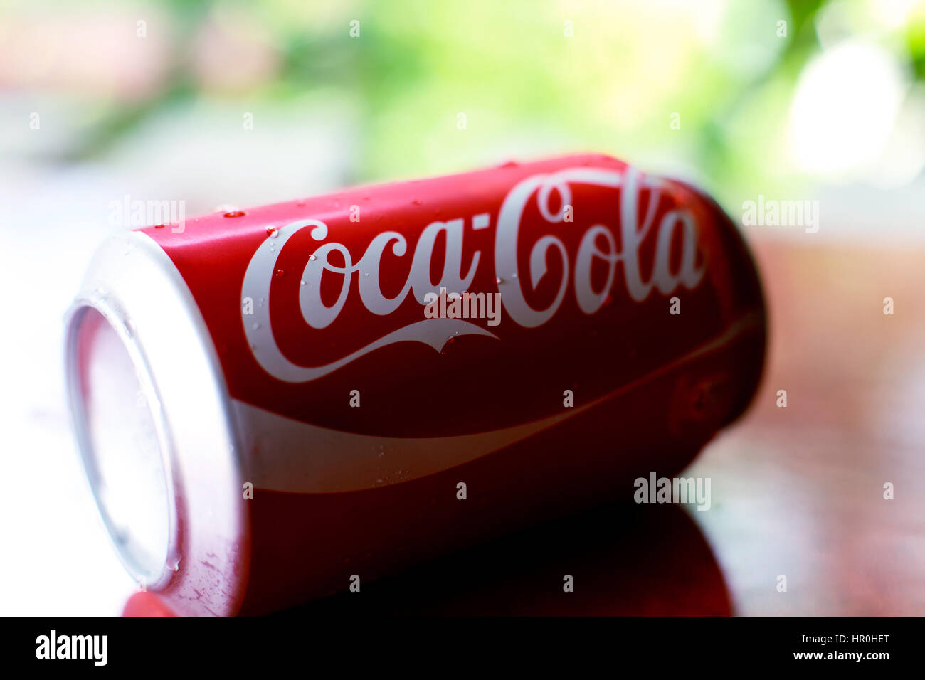SOFIA, BULGARIA -June 14, 2016. A can of Coca Cola soft drinks, close-up view ovet the soft green summer background. - Stock Image