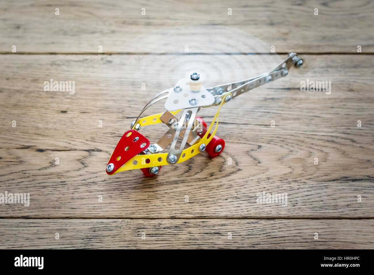Children helicopter of metal designer with spinning propeller on the wooden table - Stock Image
