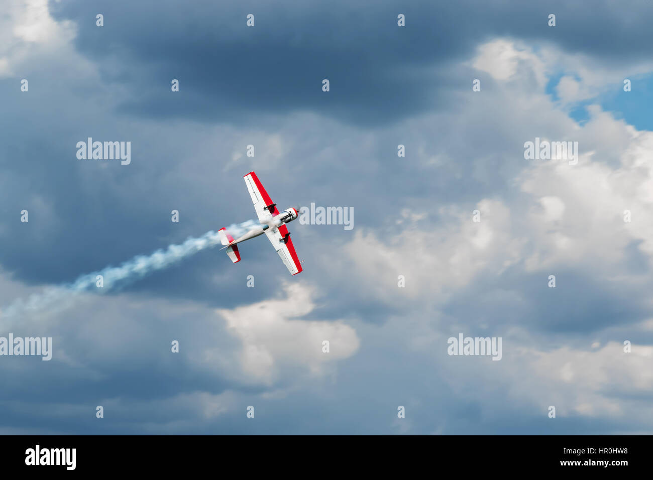 Red - white plane jets of fumes in flight in a blue sky close-up - Stock Image
