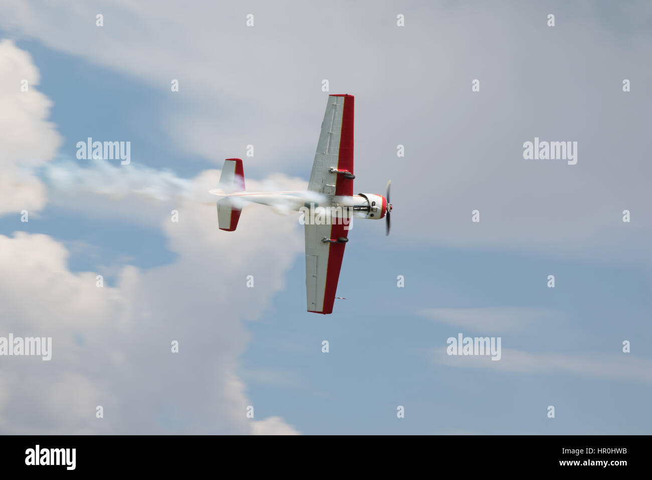 Red - white plane jets of smoke in flight in a blue sky close-up - Stock Image