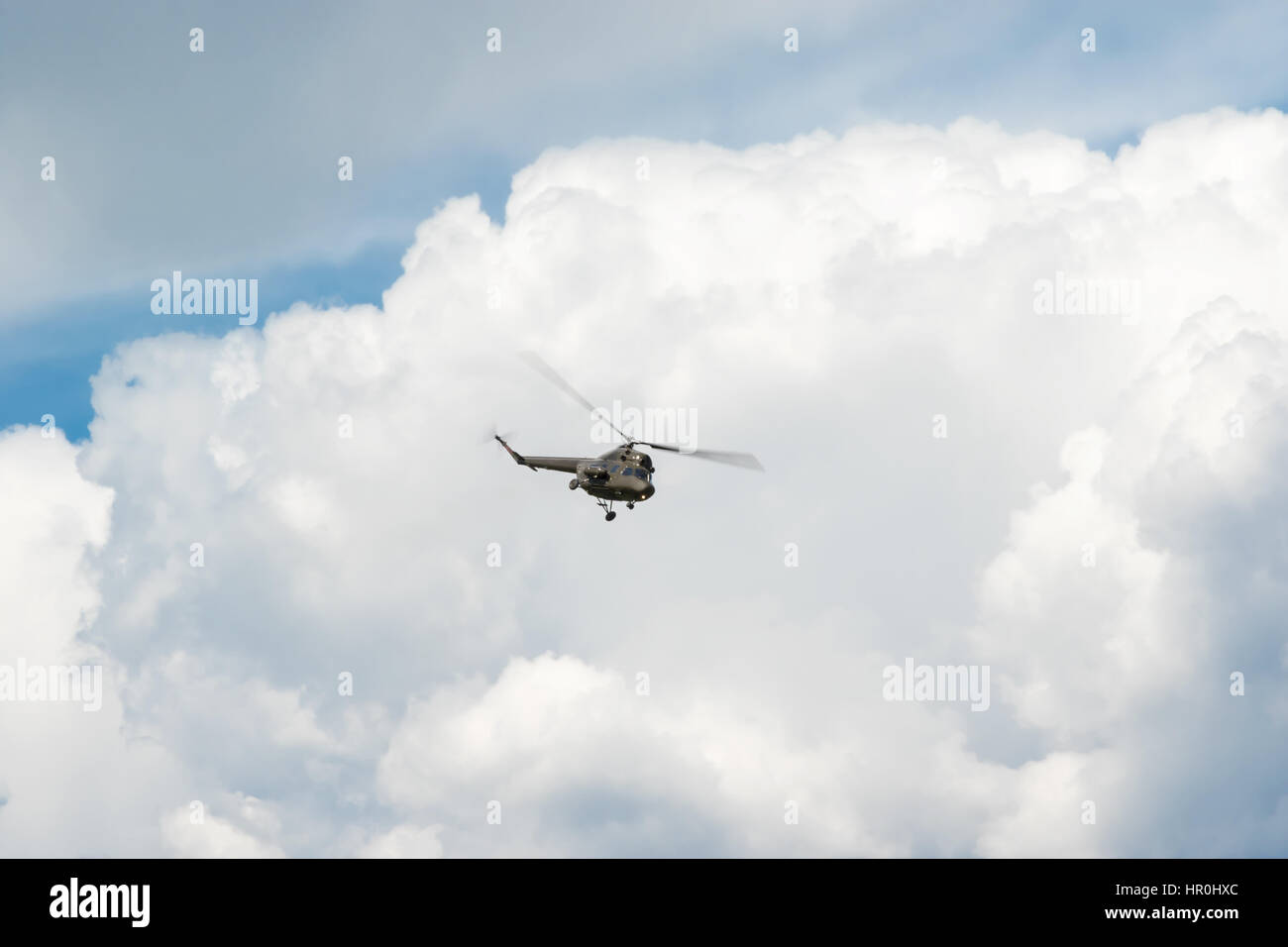 Military khaki helicopter flying in the blue sky with clouds - Stock Image