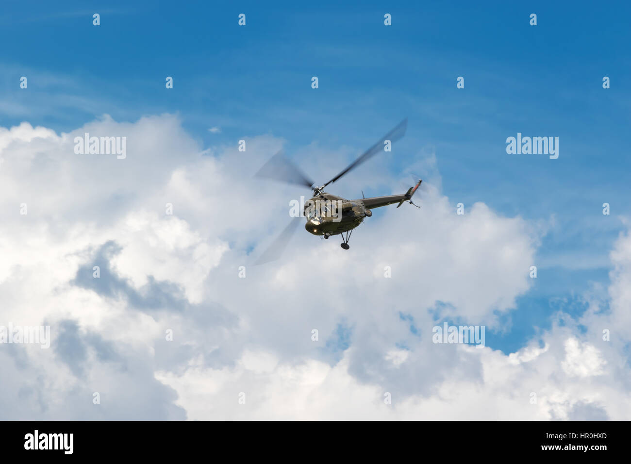 Military khaki helicopter flying in the blue sky with clouds closeup - Stock Image