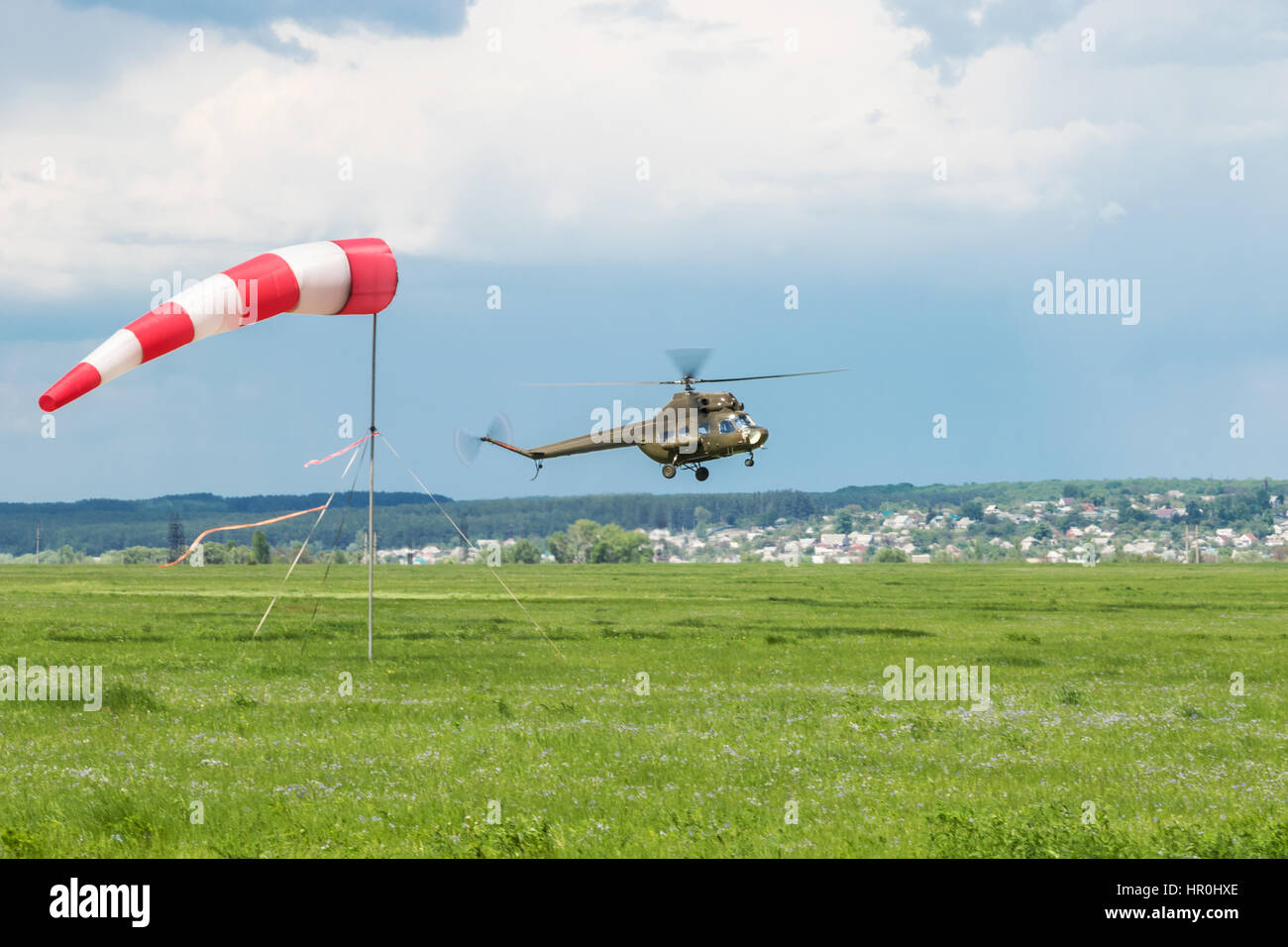 Green military helicopter flies near the ground next to a weather vane against the background of the city - Stock Image