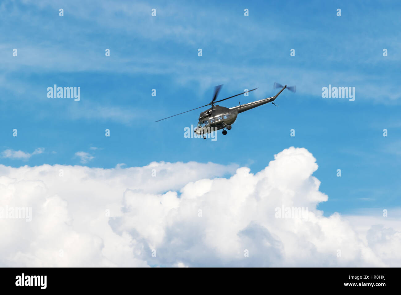 Large military helicopter flies into the side of a blue sky with clouds - Stock Image