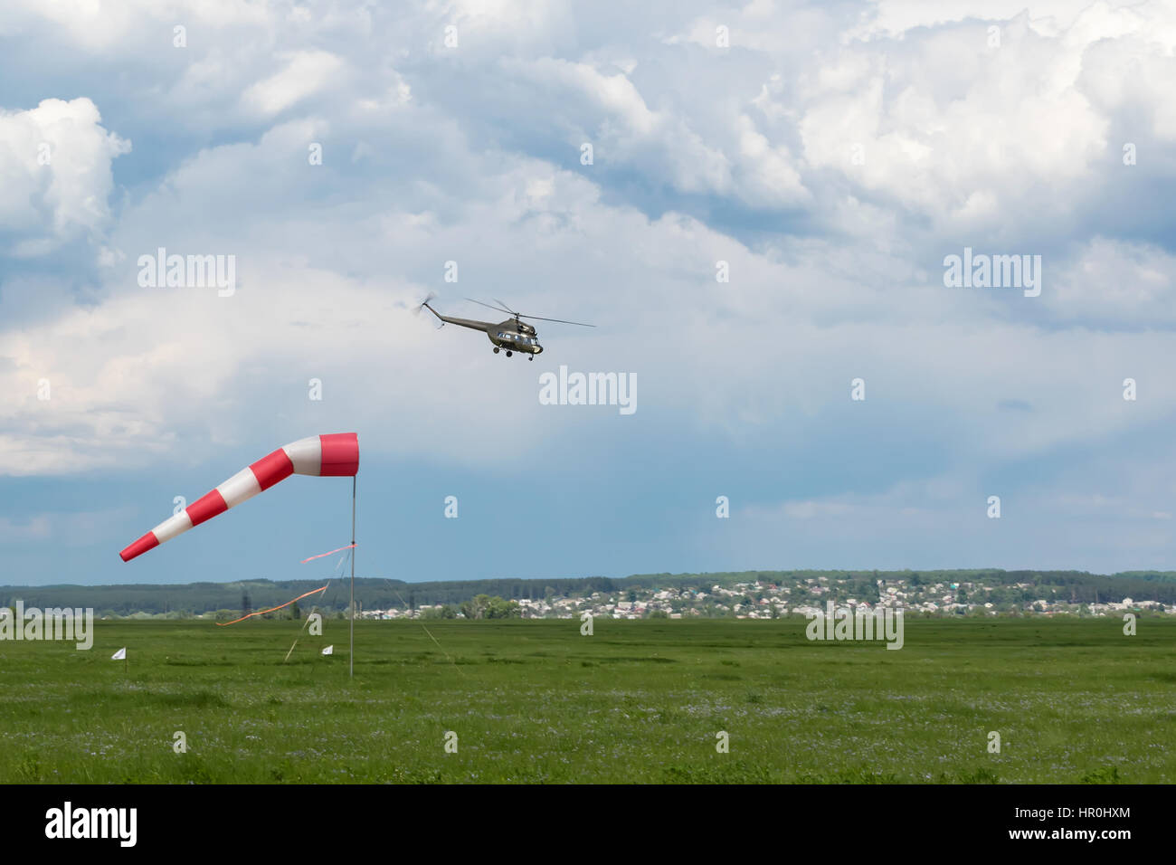 Green military helicopter flies near the ground next to a weather vane - Stock Image