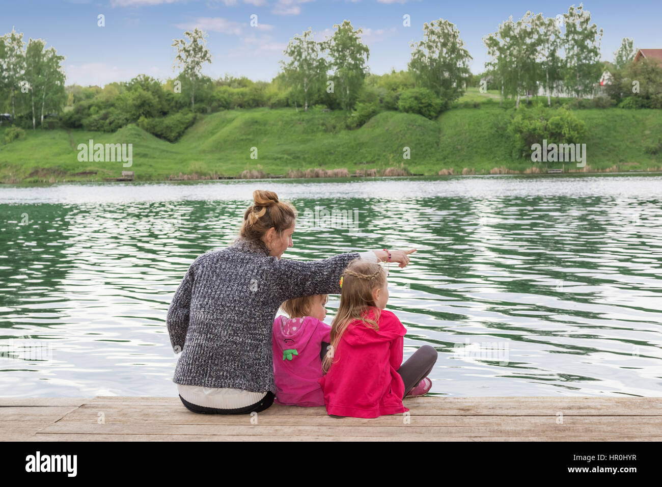 Mother of two children shows the index finger to the side sitting on a wooden plank at lake - Stock Photo