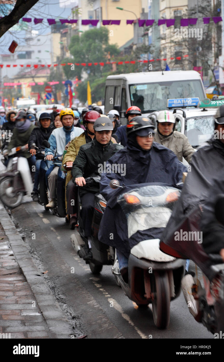 HANOI, VIETNAM - FEBRUARY 19, 2013: Crowd of people with scooters blocked in a traffic jam, waiting for green light Stock Photo