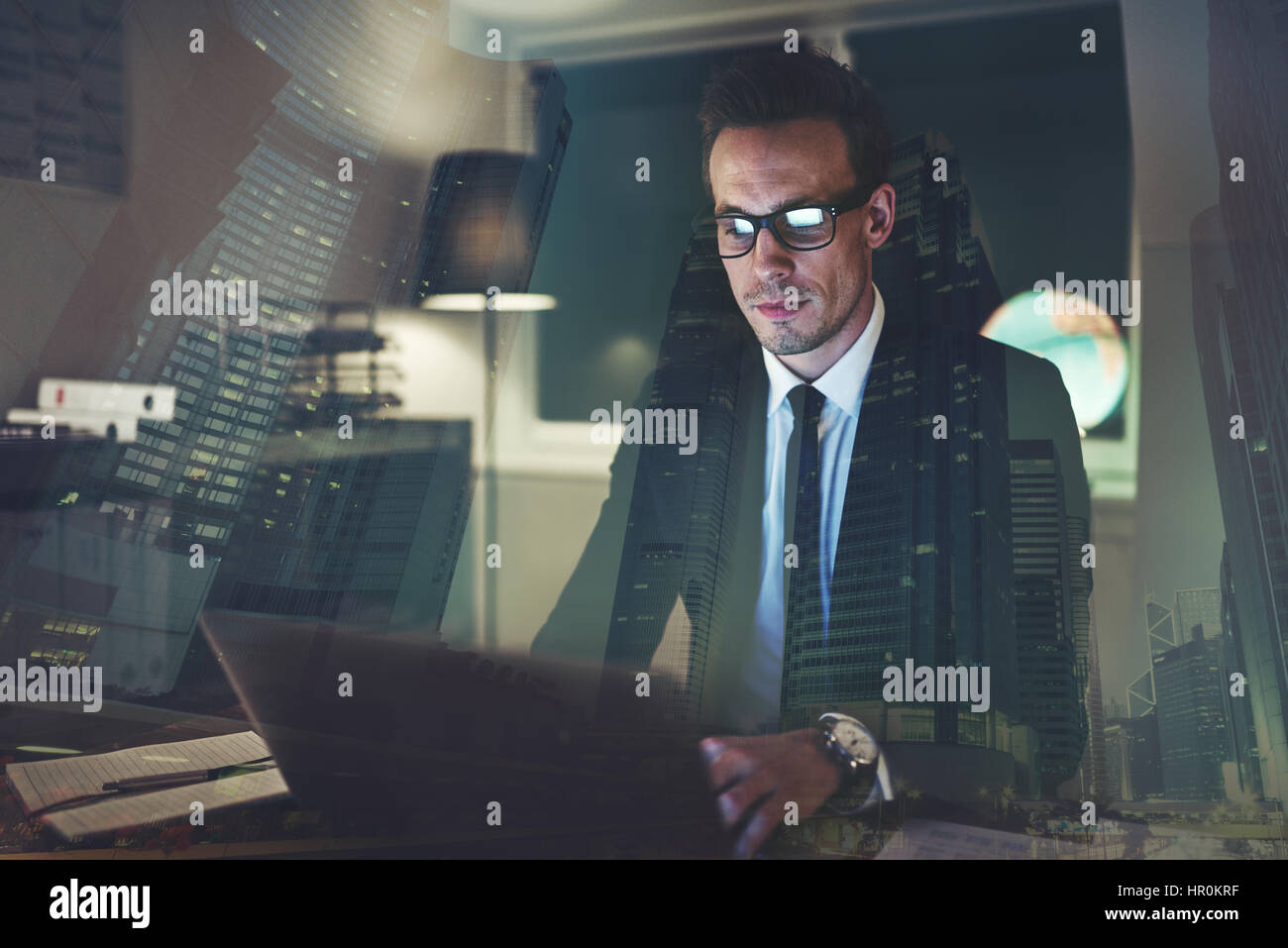 Concentrated businessman working at office at night, big city business concept - Stock Image