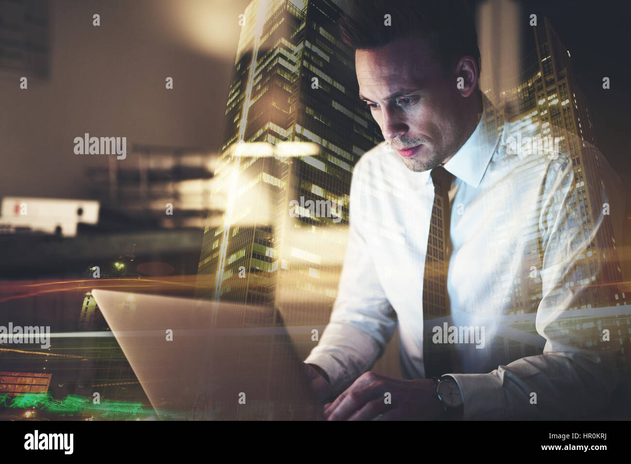 Business man sitting at his desk working on a computer and looking concentrated - Stock Image
