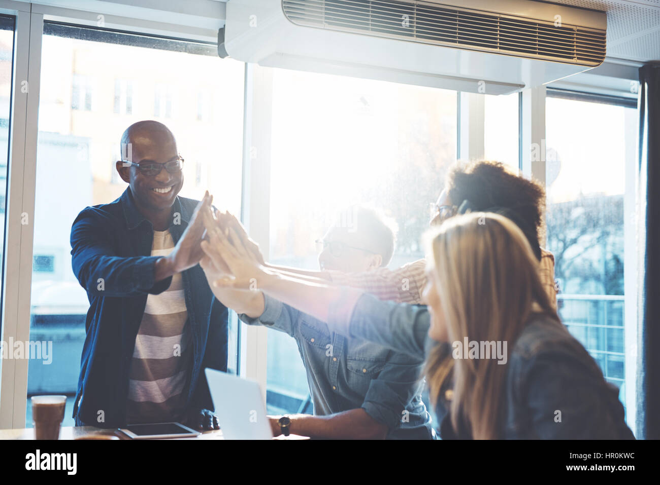 Young people in casual clothes giving high fives to each other as if celebrating something, against bright window - Stock Image